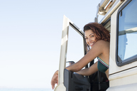 Portrait of happy woman sitting on off-road vehicle against clear sky at beach - CAVF39554