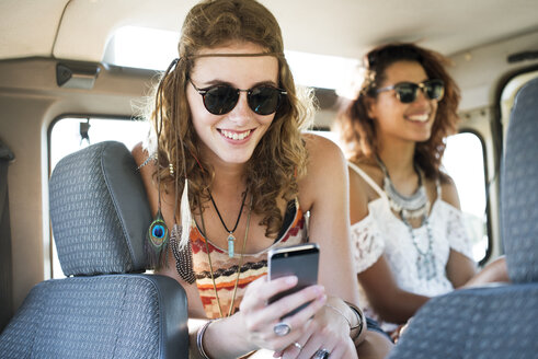 Woman using mobile phone while sitting with female friend in off-road vehicle - CAVF39572