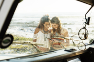 Happy friends using mobile phone at beach seen through windshield - CAVF39590