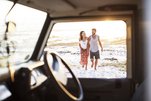 Cheerful couple walking at beach seen through window of off-road vehicle - CAVF39599