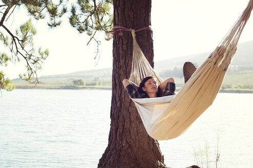 Woman sleeping on hammock by tree at lakeshore - CAVF39623