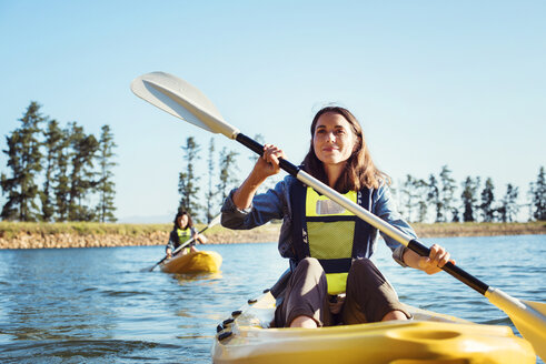 Female friends kayaking on lake against clear sky - CAVF39626