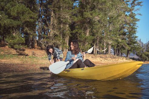 Happy female friends with kayak on lake - CAVF39638