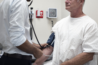 Midsection of doctor checking patient's blood pressure in hospital - CAVF39668