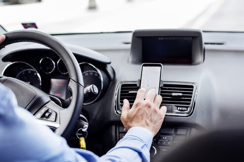Cropped image of businessman using GPS on smart phone in car - CAVF39728