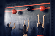 Rear view of athletes exercising with medicine balls in gym - CAVF39758