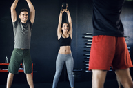 Happy athletes looking at instructor while lifting kettlebells in gym - CAVF39761