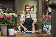 Portrait of smiling florist using tablet computer in shop - CAVF39845