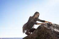 Woman rock climbing against sky on sunny day - CAVF39917