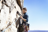Man looking at climbing rope while rock climbing against clear sky - CAVF39920