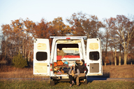 Couple looking at friend relaxing in camper van - CAVF39935