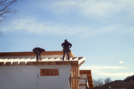 Workers constructing house roof against sky during sunny day - CAVF39980