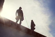 Low angle view of construction workers standing on roof beam against sky - CAVF39986