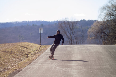 Full length of man skateboarding on country road during vacation - CAVF39989