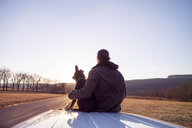 Rear view of man sitting with dog on car roof against clear sky - CAVF39998