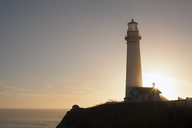 Low angle view of lighthouse on cliff against sky - CAVF40016