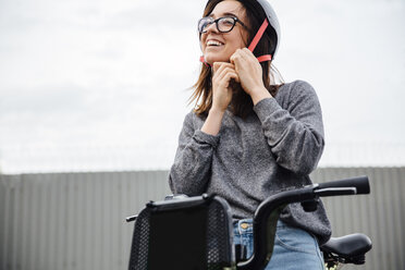 Low angle view of happy woman wearing helmet while sitting on Citi Bike - CAVF40022