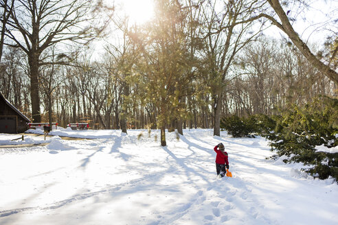 Rear view of boy walking on snow covered field at yard - CAVF40082