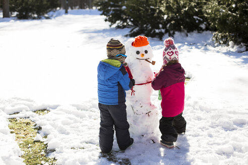 Rear view of siblings making snowman while standing on snow covered field - CAVF40094