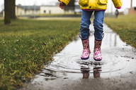 Low section of girl jumping in puddle - CAVF40097