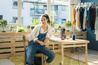 Portrait of smiling fashion designer sitting at desk in her studio - MOEF01009