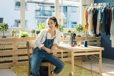 Portrait of smiling fashion designer sitting at desk in her studio - MOEF01009