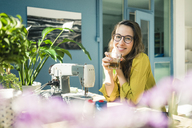 Portrait of content fashion designer sitting at desk in her studio with drink - MOEF01027