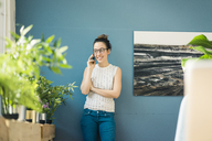 Smiling young woman on the phone at home - MOEF01033