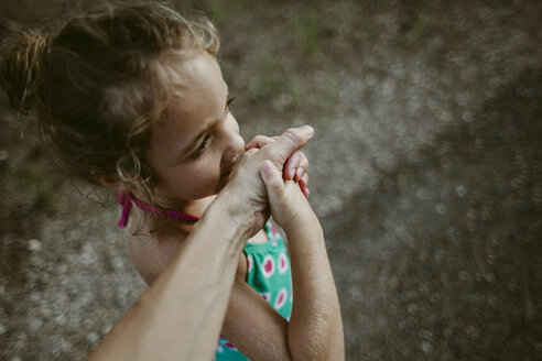 Cropped image of woman holding daughter's hand while standing on footpath - CAVF40103