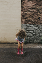 Playful girl jumping in puddle on road against wall - CAVF40124