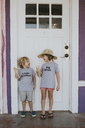 Happy siblings with ice cream looking at each other while standing against door - CAVF40130