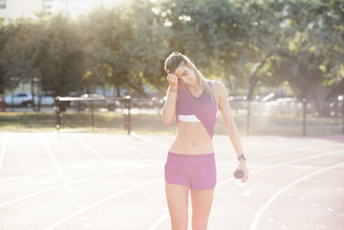 Tired female athlete wiping sweat on field - CAVF40208