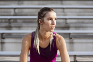 Tired female athlete sitting at stadium - CAVF40211
