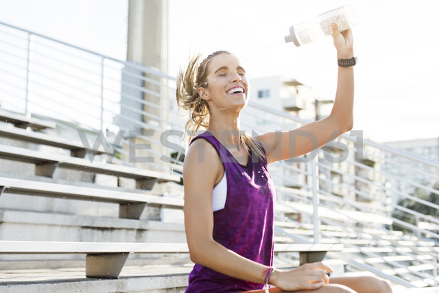 Cheerful female athlete spraying water on face while sitting on bleachers - CAVF40214 - Cavan Images/Westend61