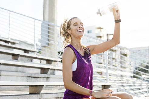 Cheerful female athlete spraying water on face while sitting on bleachers - CAVF40214