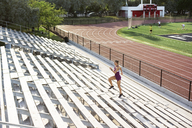 Determined female athlete running on bleachers - CAVF40217
