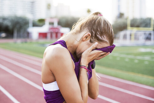 Side view of female athlete wiping sweat on face with tank top - CAVF40223