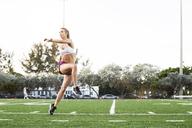 Full length of determined female athlete exercising on field - CAVF40226