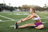 Happy female athlete touching toes while exercising on field - CAVF40229