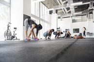 Low angle view of women exercising while dog lying in crossfit gym - CAVF40235