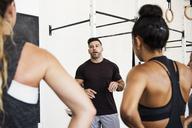 Instructor explaining athletes in crossfit gym - CAVF40238