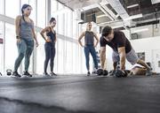 Instructor explaining athletes by doing push-ups using dumbbells in crossfit gym - CAVF40241