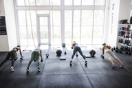 High angle view of athletes doing push-ups using dumbbells in crossfit gym - CAVF40253