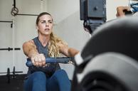Focused athlete exercising on rowing machine in crossfit gym - CAVF40262