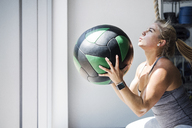 Determined female athlete exercising with medicine ball in crossfit gym - CAVF40274