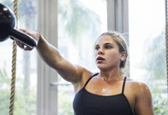 Determined athlete exercising with kettlebell in crossfit gym - CAVF40292