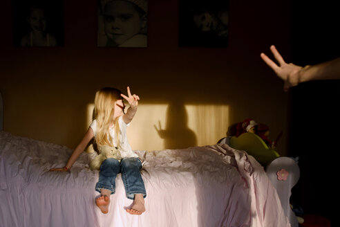 Happy girl showing peace sign while sitting on bed at home - CAVF40298