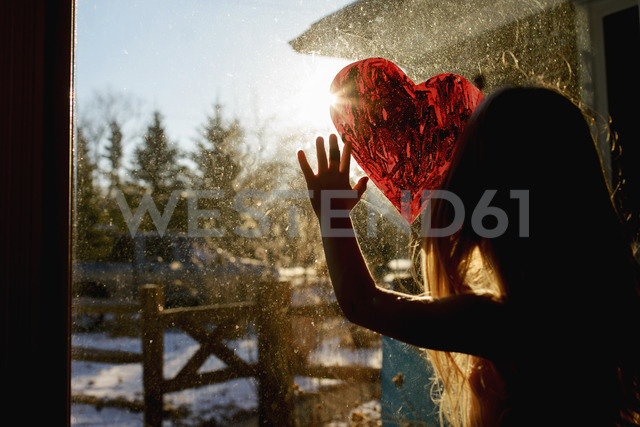 Girl drawing heart shape on window at home - CAVF40328