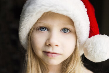 Portrait of cute girl in Santa hat against black background - CAVF40337