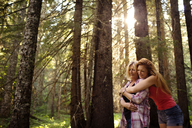 Happy mother and daughter embracing while standing amidst trees at forest - CAVF40343